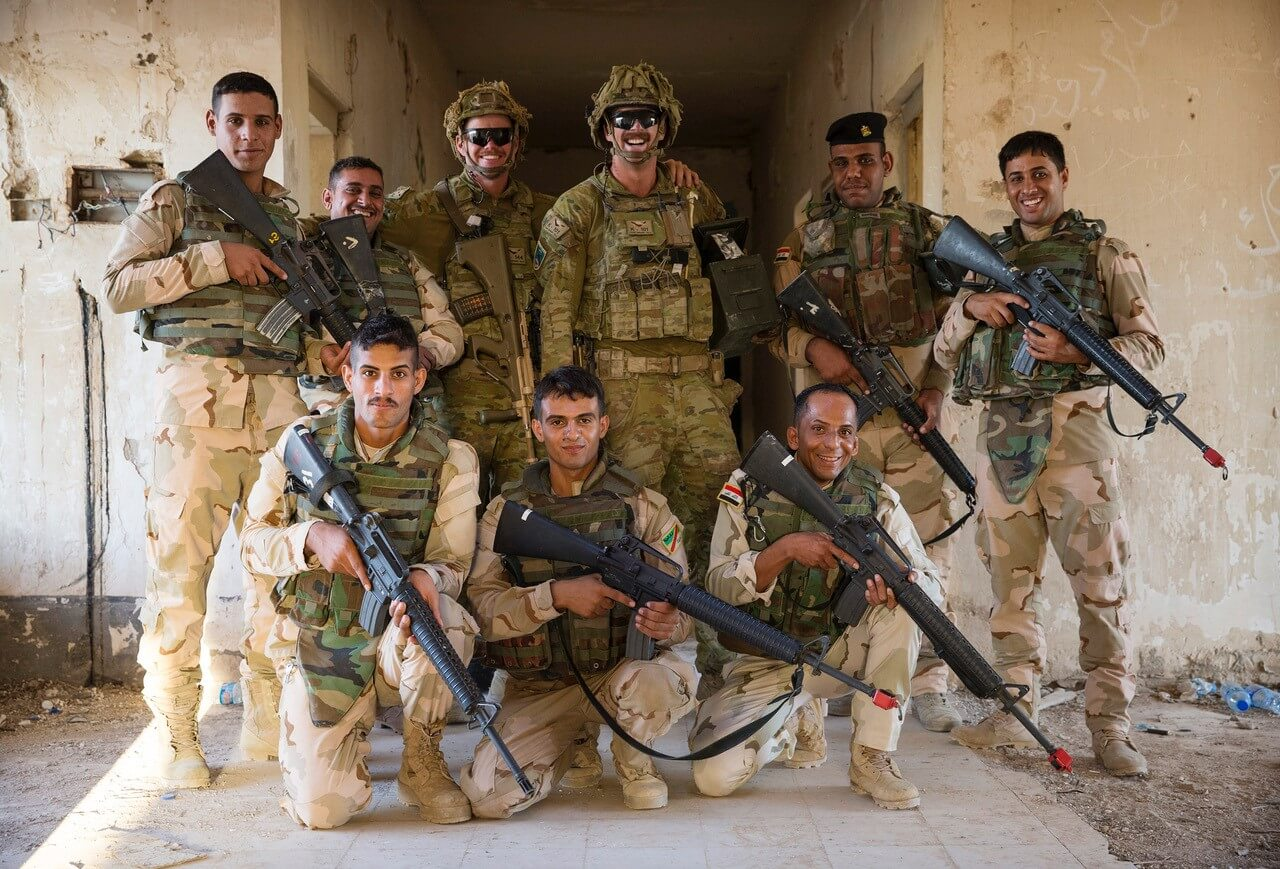 CPL Jack Dugan (centre) poses with his Iraqi Army trainees at the Urban Training Area on Camp Taji, Iraq.